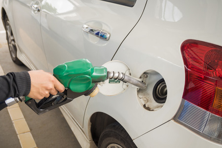 refueling: Dirty white car refueling on a gas station. Stock Photo