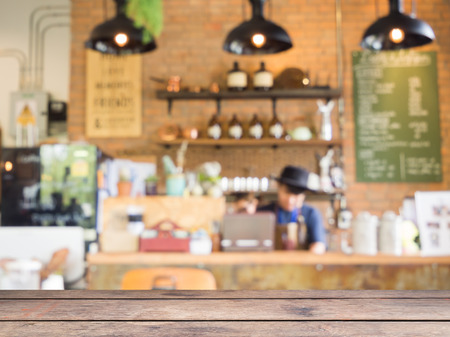 Wooden table with blurred coffee shop background