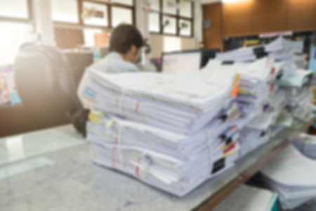 Blurred image of pile of unfinished documents on office desk with working businessman Archivio Fotografico
