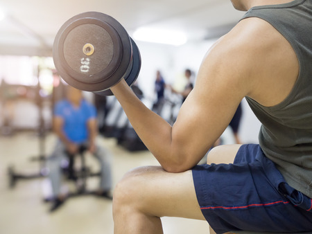 Closeup of a young athlete man lifting weights at sport club,Isolated on white background