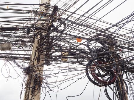 Chaos van kabels en draden op elektrische stok in Chiang Mai, Thailand.