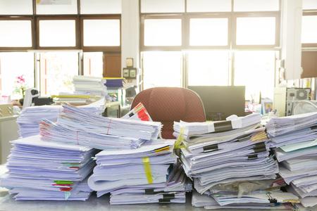 ビジネス紙のスタックのビジネス コンセプトは、オフィスの机の上の未完成の書類の山
