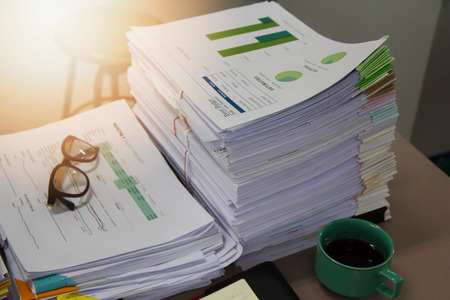 unorganized: Business Concept, Pile of unfinished documents on office desk, Stack of business paper
