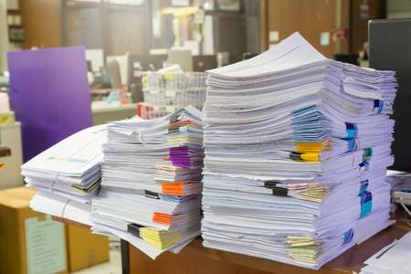 unorganized: Pile of unfinished documents on office desk, Stack of business paper