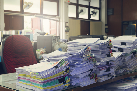 unorganized: Concept of document workload, Pile of unfinished documents on office desk, Stack of business paper, Vintage effect
