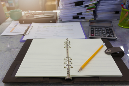 unorganized: Business and finance concept of office working, Opened blank notebook and pencil with pile of unfinished documents background