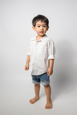 Portrait of 2 years old boy wear white shirt and shorts jean on white background. Stock Photo