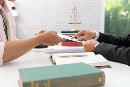 Begrippen recht, advocaat en zakenman die op kantoor werken en zakelijke contractdocumenten bespreken.