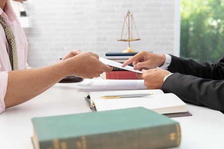 Concepts of law, Lawyer and businessman working and discussing business contract papers in office. Imagens
