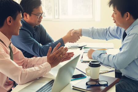 Business and finance concept of office working,Teamwork of Businessmen shaking hand after deal investment business plan in office