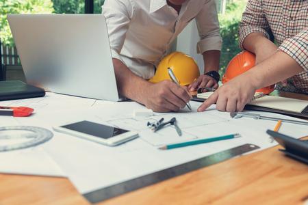 Concepto de Ingeniero y Arquitecto, equipo de oficina de Ingenieros Arquitectos trabajando con planos
