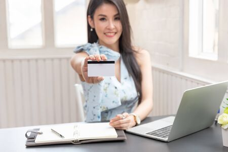 Freelancer business woman holding credit cart to shopping online with computer laptop in cafe. 版權商用圖片