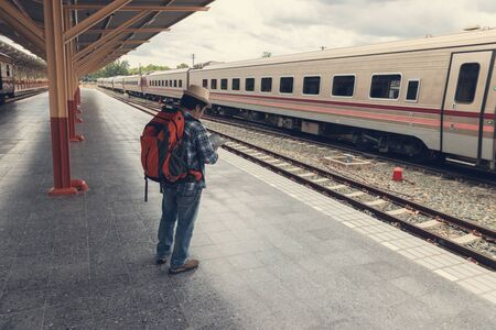 Asian traveler man with belongings waiting for travel by train at Chiang Mai train station, Thailand 版權商用圖片