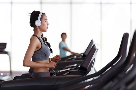 Fitness woman wearing headphone cardio workout at fitness gym.