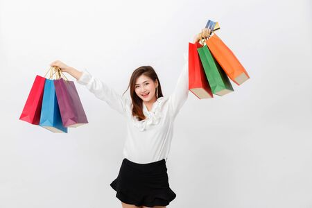 Portrait of beautiful woman holding shopping bags and credit card over white background