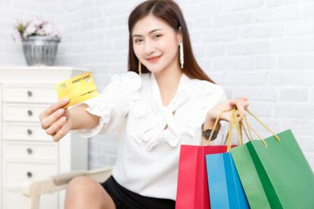 Credit card payment service. Woman customer carrying shopping bag and using credit card paying for order in shopping mall