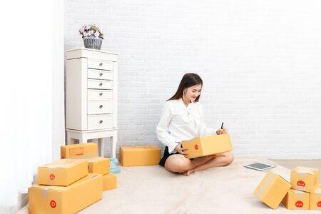Young teenage prepare to send goods to customer after checking order, work at home. Stock fotó
