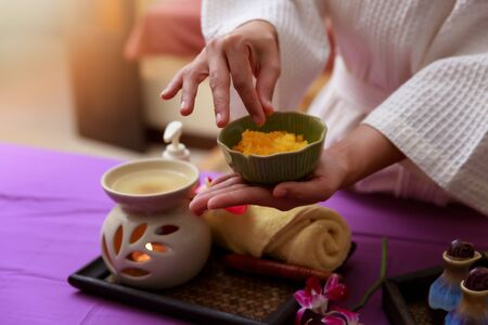 Asian woman holding salt scrub for massage at spa.