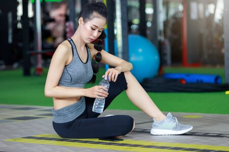 Fitness woman wearing headphone drinking water after cardio workout at fitness gym. Stock Photo