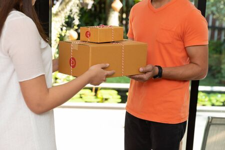 Customer receiving parcel from delivery courier at home.