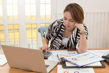 Businesswoman using calculator to calculate asset value and investment profit Stock fotó