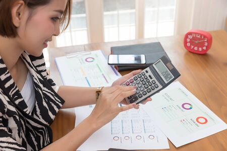 Businesswoman using calculator to calculate sale analysis Chart and investment profit
