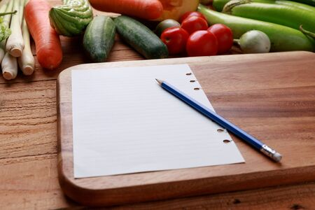 Thai kitchen. Various vegetables, spices  and Ingredients with blank notebook and pencil on wooden background.