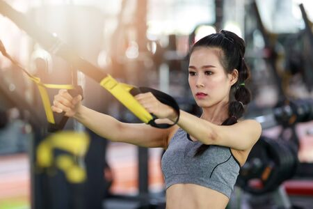 Fitness woman exercise with exercise-machine Cable Crossover in gym
