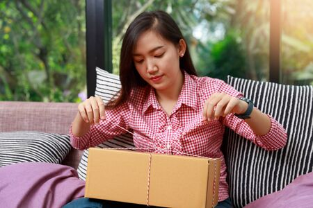 Happy woman opening parcel box at home 版權商用圖片