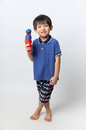 Welcome Thailand Songkran festival, Portrait of Asian boy wearing flower shirt smiled with water gun on white background. Archivio Fotografico - 140895882