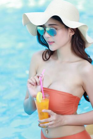 Beautiful female in bikini relaxing at the pool with cocktail. 版權商用圖片