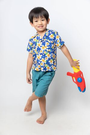 Welcome Thailand Songkran festival, Portrait of Asian boy wearing flower shirt smiled with water gun on white background.