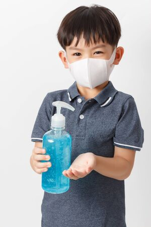 Asian boy wearing a protection mask and holding bottle of alcohol gel for cleaning baby hands to prevent against infection of Covid-19 outbreak.