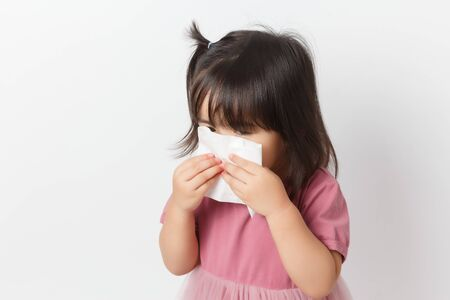 Little asian girl holding a tissue and blow her nose. Kid with cold rhinitis. virus and infection. Coronavirus symptom