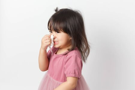 Little asian girl holding a tissue and blow her nose. Kid with cold rhinitis. virus and infection. Coronavirus symptom Standard-Bild