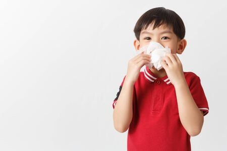 Little asian boy holding a tissue and blow his nose. Kid with cold rhinitis. virus and infection. Coronavirus symptom