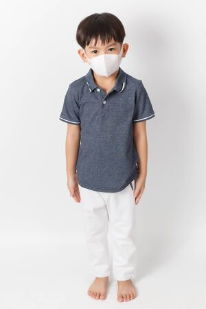 Asian child boy wearing a protection mask for prevent against infection of Covid-19 virus outbreak or dust PM 2.5 air pollution. Standard-Bild