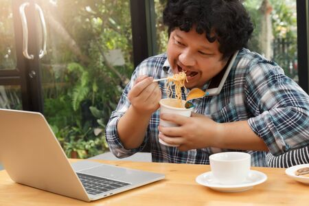 Work from home,Businessman working remotely from home. Using computer and eating cup noodle. Distance learning online education and work