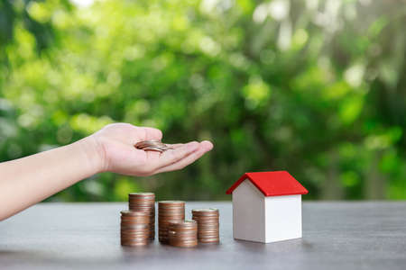 Property investment and house mortgage financial concept, Asian boy holding money and coin stack with house model on green background.