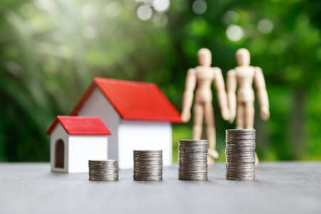 Property investment and house mortgage financial concept, Coin stack and wooden dolls with house model on green background.