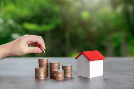 Property investment and house mortgage financial concept, Asian boy putting money to coin stack with house model on green background. Standard-Bild