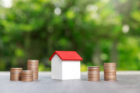 Property investment and house mortgage financial concept, Coin stack with house model on green background. Standard-Bild - 151397554