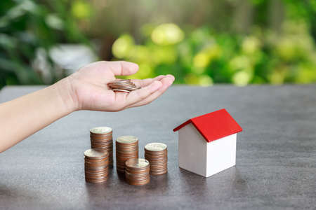Property investment and house mortgage financial concept, Asian boy holding money and coin stack with house model on green background. Standard-Bild - 151397556