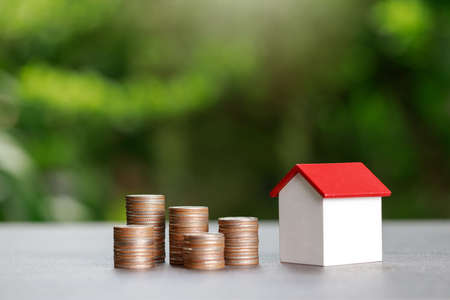 Property investment and house mortgage financial concept, Coin stack with house model on green background.