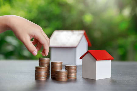 Property investment and house mortgage financial concept, Asian boy putting money to coin stack with house model on green background. Stock Photo