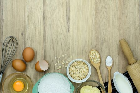 tools and ingredients for baking cake (flour, butter, eggs, milk, Oatmeal) on wooden background. Top view with copy space. Stok Fotoğraf