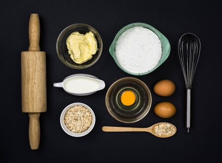 tools and ingredients  for the dough (flour, butter, eggs, milk, Oatmeal) on black background. Top view.