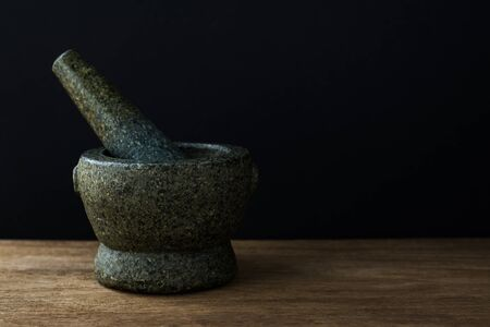 Stone Mortar on the wooden table,Black background with copy space