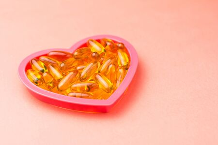 Fishoil capsules in the heart shape frame on pink background with copy space.