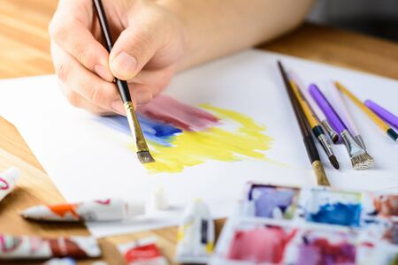 Close up of male artist's hand painting water color with blured Palette with color foreground Stok Fotoğraf